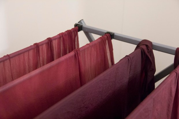 The finished fabric dries on a rack, dripping in the bath tub
