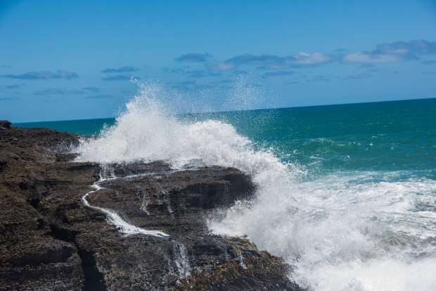 wave crashes against rocks at piha new zealand